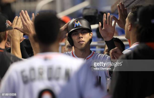 Christian Yelich of the Miami Marlins is congratulated after scoring on a past ball during a game against the Philadelphia Phillies at Marlins Park...