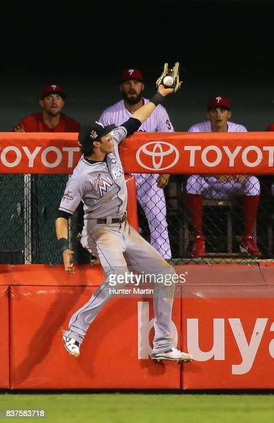 Christian Yelich of the Miami Marlins makes a leaping catch over the fence to save a home run in the fifth inning during game two of a doubleheader...
