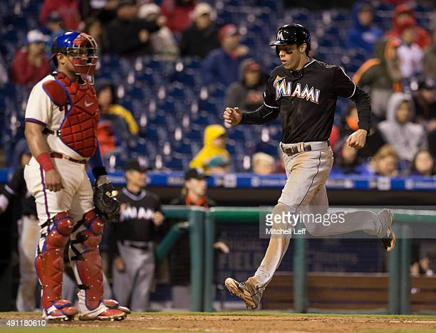 Christian Yelich of the Miami Marlins scores a run past Carlos Ruiz of the Philadelphia Phillies in the top of the ninth inning on October 3 2015 at...