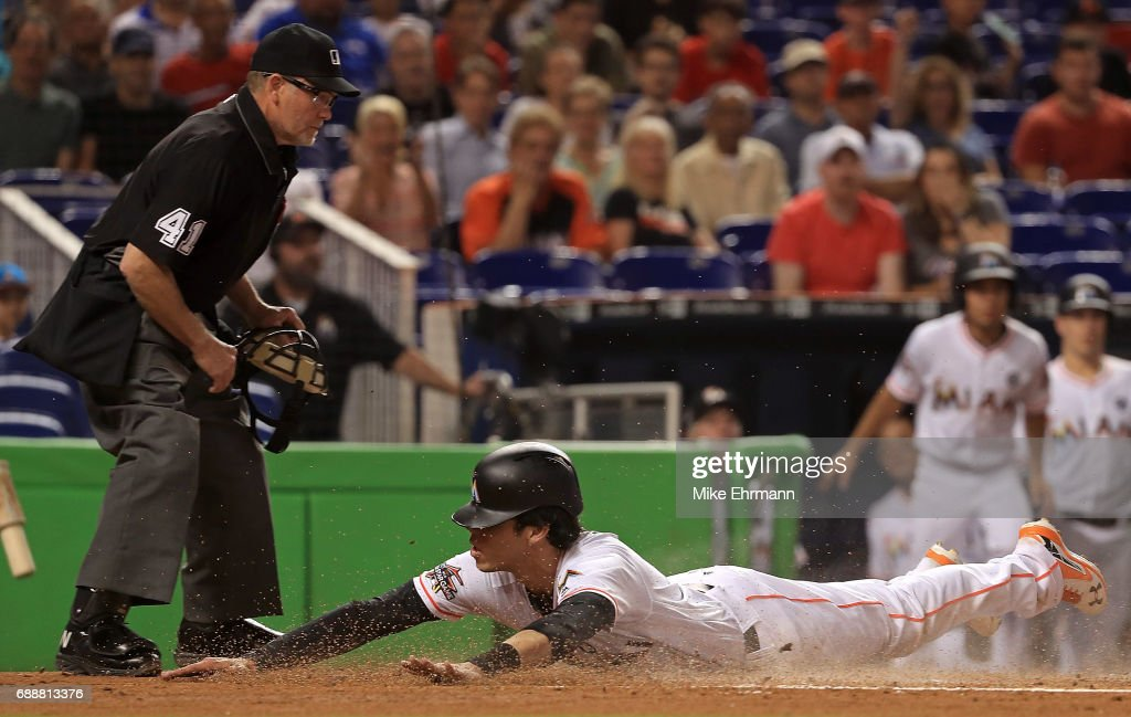 Christian Yelich #21 of the Miami Marlins slides into home to score a run past the tag from Martin Maldonado #12 of the Los Angeles Angels in the first inning during a game against the Los Angeles Angels at Marlins Park on May 26, 2017 in Miami, Florida.
