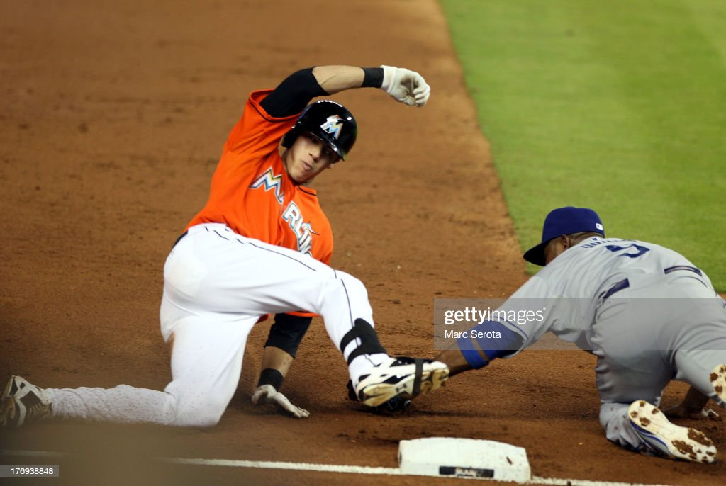 Christian Yelich #21 of the Miami Marlins slides into third after hitting an RBI triple in the second inning against the Loos Angeles Dodgers at Marlins Park on August 19, 2013 in Miami, Florida.