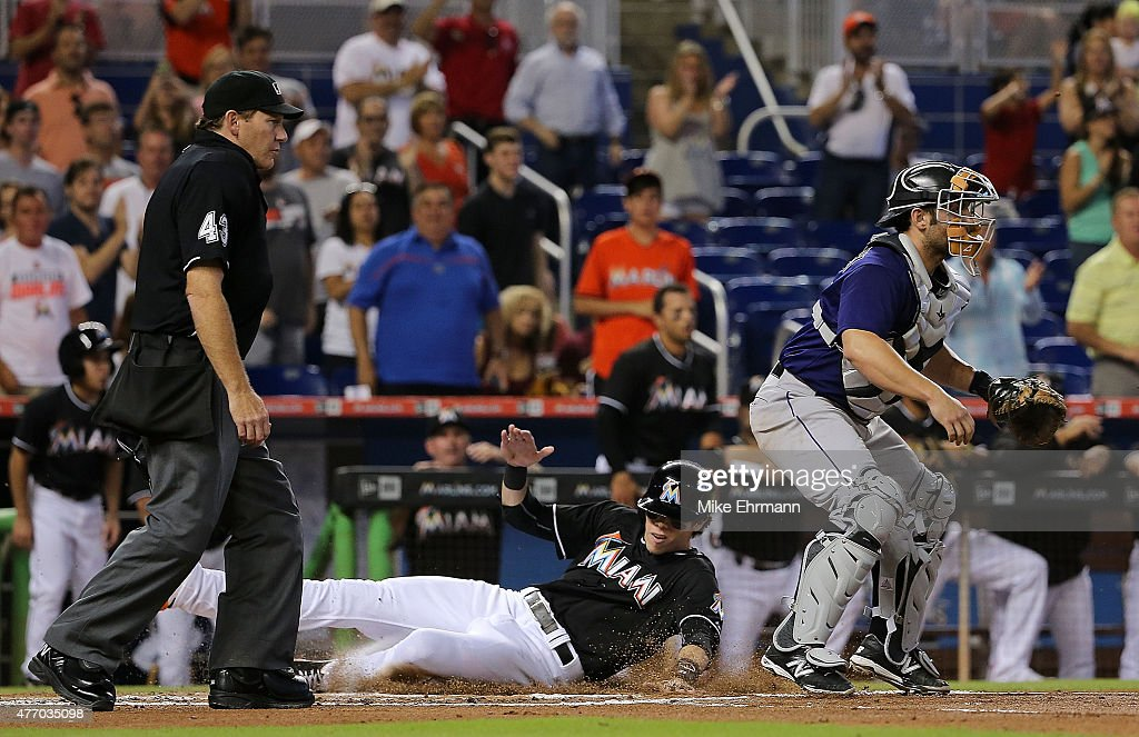 <a gi-track='captionPersonalityLinkClicked' href=/galleries/search?phrase=Christian+Yelich&family=editorial&specificpeople=9527291 ng-click='$event.stopPropagation()'>Christian Yelich</a> #21 of the Miami Marlins slides past <a gi-track='captionPersonalityLinkClicked' href=/galleries/search?phrase=Michael+McKenry&family=editorial&specificpeople=4949028 ng-click='$event.stopPropagation()'>Michael McKenry</a> #8 of the Colorado Rockies after scoring on a two RBI double by Giancarlo Stanton #27 during a game at Marlins Park on June 13, 2015 in Miami, Florida.