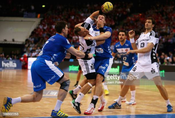 Christian Zeitz of Kiel challenged by Daniel Kubes and Felix Danner of Melsungen during the Lufthansa Final Four SemiFinal between MT Melsungen and...