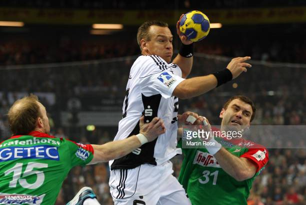Christian Zeitz of Kiel challens Yves Grafenhorst and Bartosz Jurecki of Magdeburg during the Toyota Handball Bundesliga match between THW Kiel and...