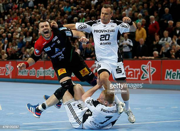 Christian Zeitz of Kiel fouls Bartosz Jureki of Magdeburg during the Bundesliga handball match between THW Kiel and SC Magdeburg at the Sparkassen...