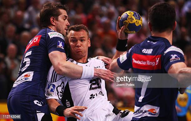 Christian Zeitz of Kiel is challenged by Gillaume Gille and Matthias Flohr of Hamburg during the Toyota Handball Bundesliga match between THW Kiel...
