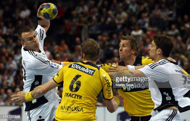 Christian Zeitz of Kiel is challenged by Grzegorz Tkaczyk and Oliver Roggisch of RheinNeckar during the Toyota Handball Bundesliga match between THW...