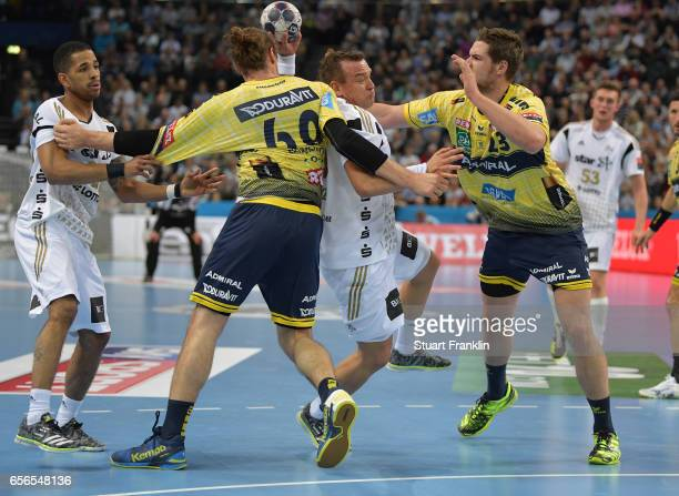 Christian Zeitz of Kiel is challenged by Hendrik Pekeler and Kim Ekdahl Du Rietz of Rhein Neckar during the first leg round of 16 EHF Champions...