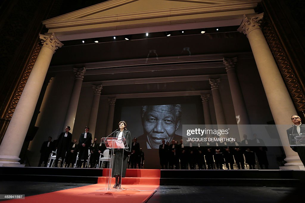 Christiane Feral-Schuhl, president of the Paris Bar and Parisian lawyers observe a minute of silence to mark the passsing of late South African President Nelson Mandela (seen on screen) during a solemn session of the return of the Paris bar association on December 6, 2013 at the Theatre du Chatelet in Paris. Mandela, the revered icon of the anti-apartheid struggle in South Africa and one of the towering political figures of the 20th century, has died on December 5 aged 95. Mandela, who was elected South Africa's first black president after spending nearly three decades in prison, had been receiving treatment for a lung infection at his Johannesburg home since September, after three months in hospital in a critical state.