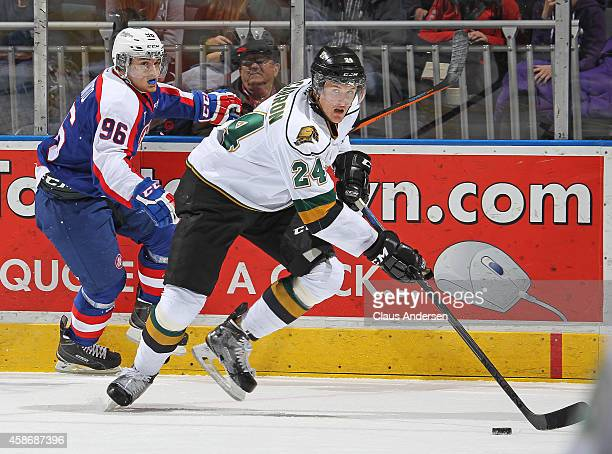 Christiano DiGiacinto of the Windsor Spitfires skates to check Michael McCarron of the London Knights in an OHL game at Budweiser Gardens on November...