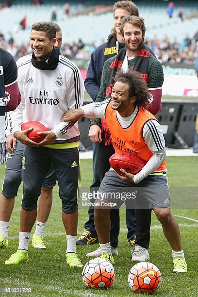 Christiano Ronaldo and Marcelo of Real Madrid react while holding an AFL football during a Real Madrid training session at Melbourne Cricket Ground...