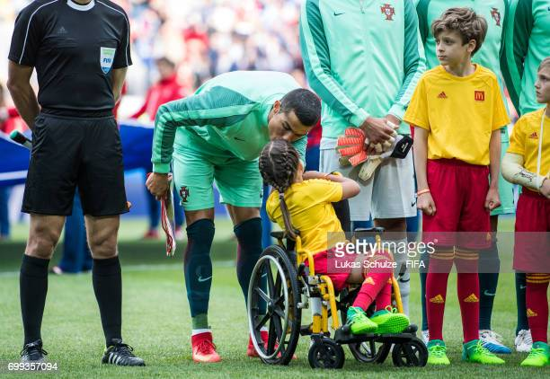 Christiano Ronaldo of Portuga kisses a McDonalds mascot girl in a wheel chair prior to the FIFA Confederations Cup Russia 2017 Group A match between...