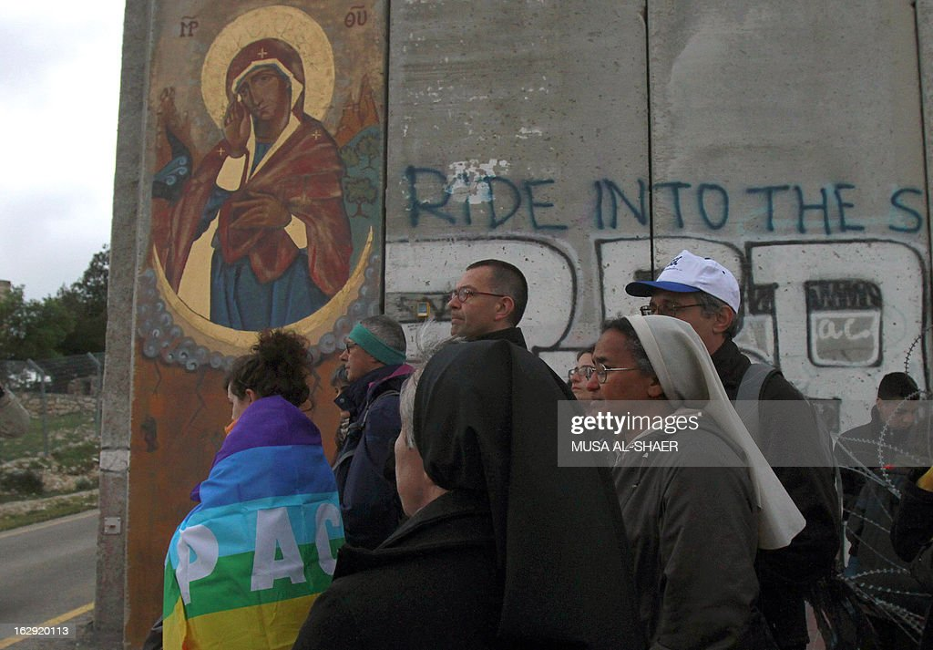 Christians gather to pray at Israel's controversial separation barrier decorated to resemble an icon of the Virgin Mary on the outskirts of the biblical town of Bethlehem, in the Israeli occupied West Bank, on March 1, 2013. In a non-binding 2004 judgment, the International Court of Justice called for the dismantling of all parts of the separation barrier built on Israeli occupied Palestinian territory.