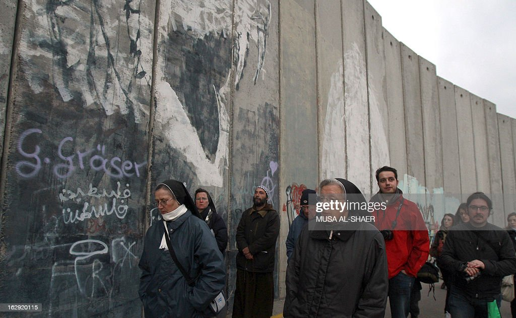 Christians gather to pray at Israel's controversial separation barrier on the outskirts of the biblical town of Bethlehem, in the Israeli occupied West Bank, on March 1, 2013. In a non-binding 2004 judgment, the International Court of Justice called for the dismantling of all parts of the separation barrier built on Israeli occupied Palestinian territory.