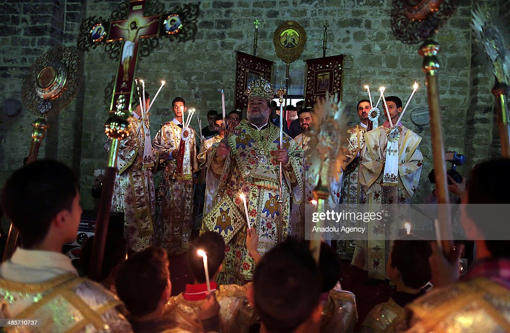 Christians pray during the Easter Celebration ceremony in Saint Porphyrius Orthodox Christian church of Gaza on April 19, 2014.