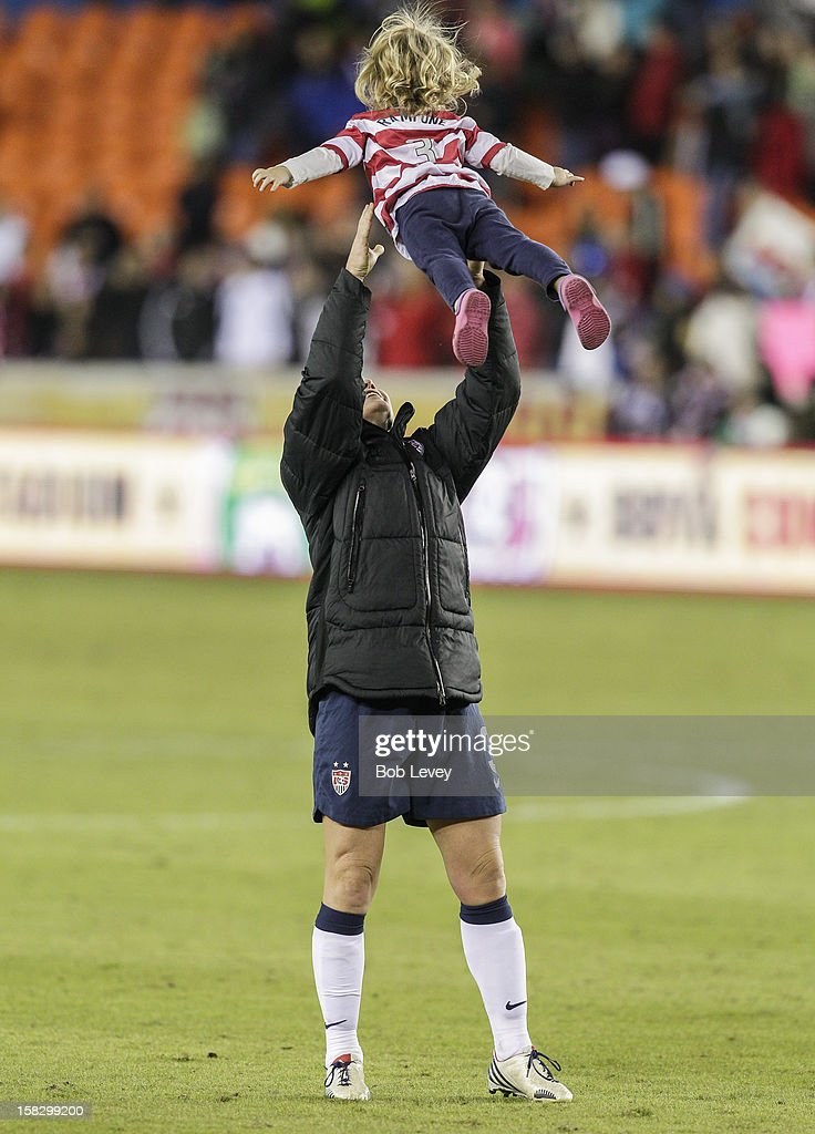 Christie Rampone (3) of the United States lifts her daughter, Reece Elizabeth up after defeating of China in the second half at BBVA Compass Stadium on December 12, 2012 in Houston, Texas. USA won 4-0.