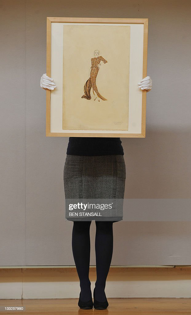 A Christie's auction house employee poses for pictures with a costume sketch for Marlene Dietrich's gold ensemble worn to attend the opera as 'Maria Barker' in the film 'Angel', (1937) during a photocall at the auction house in London, on November 18, 2011. The sketch is expected to fetch in the region of GBP 5,000-7,000 (approx 5,825-8,150 euros/7,900-11,000 USD) during Christies' London sale of Film and Entertainment Memorabilia on November 23, 2011. AFP PHOTO/BEN STANSALL