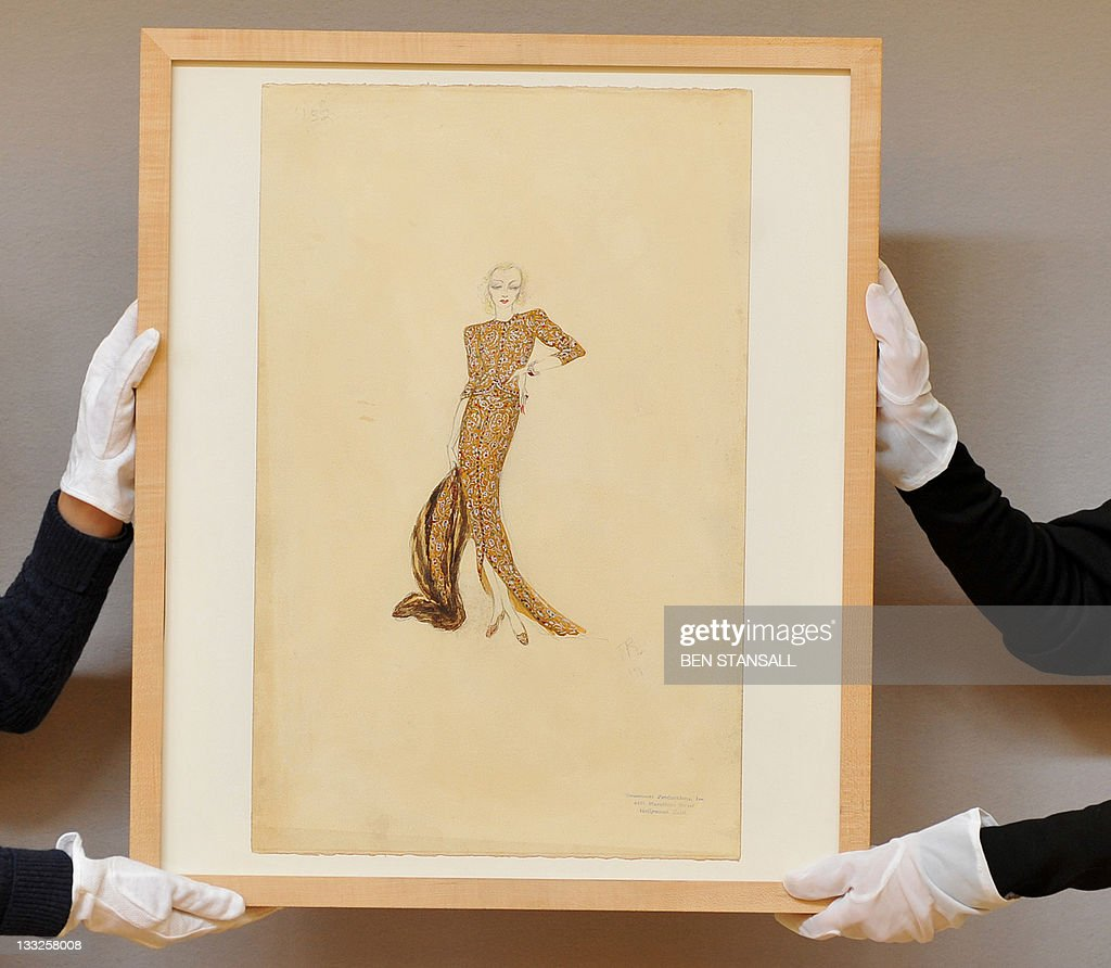 A Christie's auction house employee poses for pictures with a costume sketch for Marlene Dietrich's gold ensemble worn to attend the opera as 'Maria Barker' in the film 'Angel', (1937) during a photocall at the auction house in London, on November 18, 2011. The sketch is expected to fetch in the region of GBP 5,000-7,000 (approx 5,825-8,150 euros/7,900-11,000 USD) during Christies' London sale of Film and Entertainment Memorabilia on November 23, 2011.