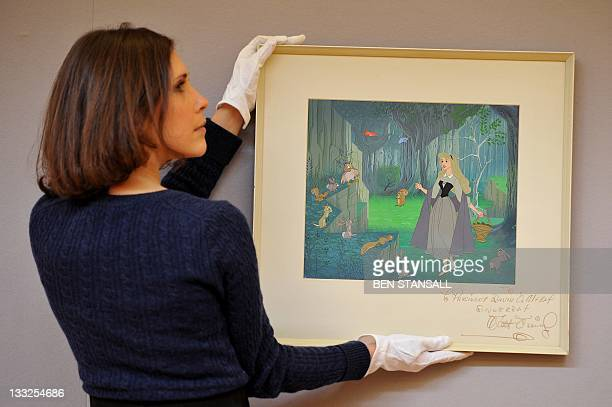 A Christie's auction house employee poses for pictures with a signed Disney animation celluloid with original hand painted production background for...