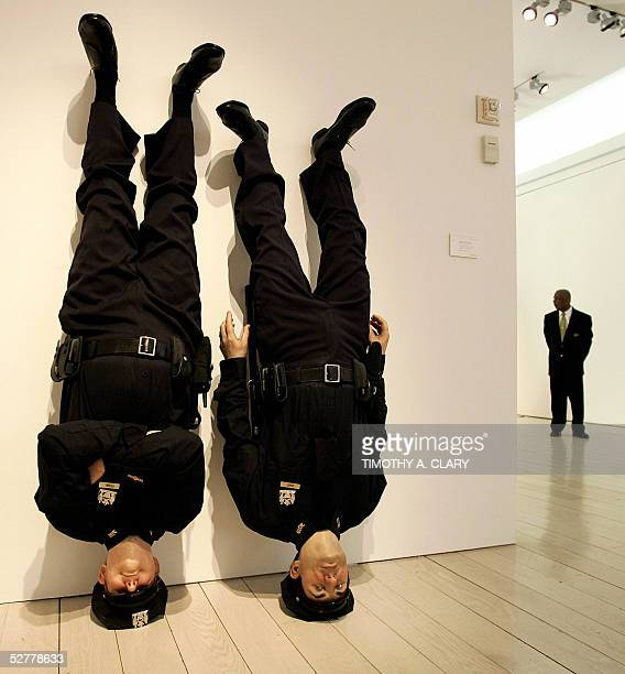 Christie's auction house security guard keeps an eye on full size NYPD wax figures ' Frank and Jamie' by Maurizio Cattelan during the preview of...