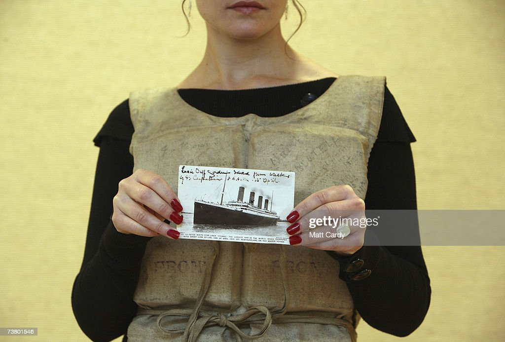 Christies employee Ansie Els wears a Titanic life-preserver, which was worn by Titanic survivor Miss Mabel Francatelli, while holding up a postcard written by Miss Francatelli on April 4 2007 in London. The life-preserver is part of a Maritime sale of memorabilia from the 1912 disaster and is estimated to sale for 50,000 to 80,000 pounds.