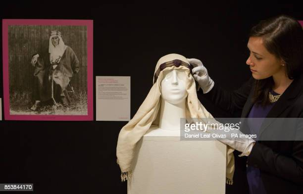 A Christie's employee arranges an ivory silk headdress owned by T E Lawrence which is part of the Famous and Infamous exhibition which includes...