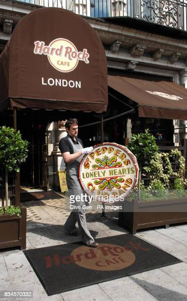 A Christie's employee carries the Beatles drumskin which appeared in the LP cover of Sgt Pepper's Lonely Hearts Club Band out of The Hard Rock Cafe...