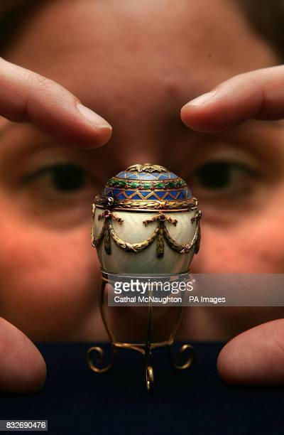 A Christie's employee holds a Faberge decorative enamel and two gold egg bonbonniere at their auction house in central London