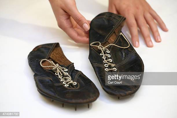 Christie's employee holds running shoes worn by Sir Roger Bannister when he became the first man in history to run one mile in under 4 minutes on May...