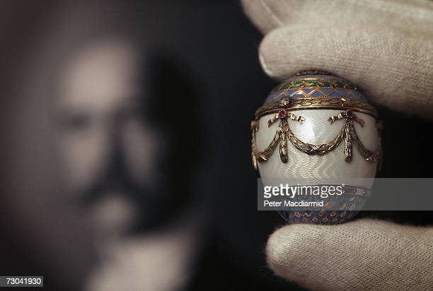 Christie's employee holds up a Faberge enamel and two colour gold egg bonbonniere estimated at GBP30000 GBP50000 infront of a portrait of King George...