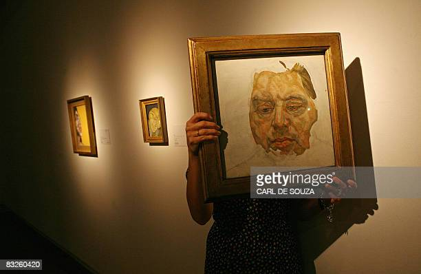 A Christie's employee holds up a portrait of Francis Bacon by British artist Lucian Freud at Christie's auction house in London on October 14 2008...