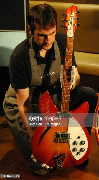 A Christie's employee holds up Paul Weller's 1974 Rickenbacker 330 guitar which is expected to fetch between 5000 6000 when it goes under the hammer...