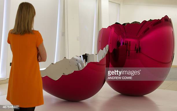 A Christie's employee looks at a piece entitled 'Cracked egg ' by US artist Jeff Koons at Christie's in central London on February 7 2014 Cracked Egg...