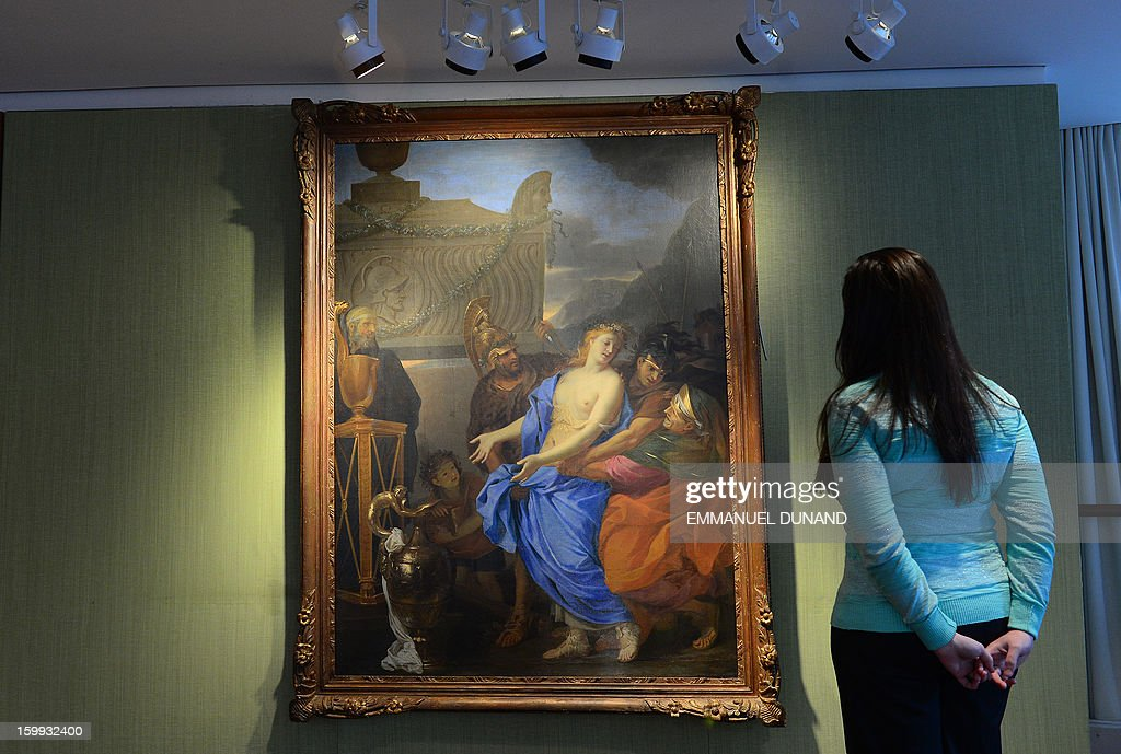 A Christie's employee looks at an oil painting by 17th century artist Charles Le Brun is on display at Christie's in New York, January 23, 2013. A major renovation at Paris's legendary Ritz hotel has resulted in the discovery of the painting that nobody knew was there. Now, the giant tableau is to be sold by Christie's auctioneers and could raise up to 500,000 euros ($665,000) for the foundation established by owner Mohamed Al Fayed in memory of his son Dodi, the late boyfriend of Princess Diana. The oil painting has been identified by experts as an early work by Le Brun (1619-1690) that would have been completed before he became the official painter at the court of Louis XIV and established his reputation as one of the dominant figures of 17th century French art. AFP PHOTO/Emmanuel Dunand 'MANDATORY MENTION OF THE ARTIST UPON PUBLICATION'