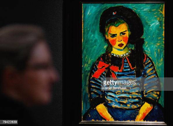 Christies employee looks on as Kees Van Dongen's Anita Aux Fleurs hangs on the wall during a press preview for Christies London sale in impressionist...