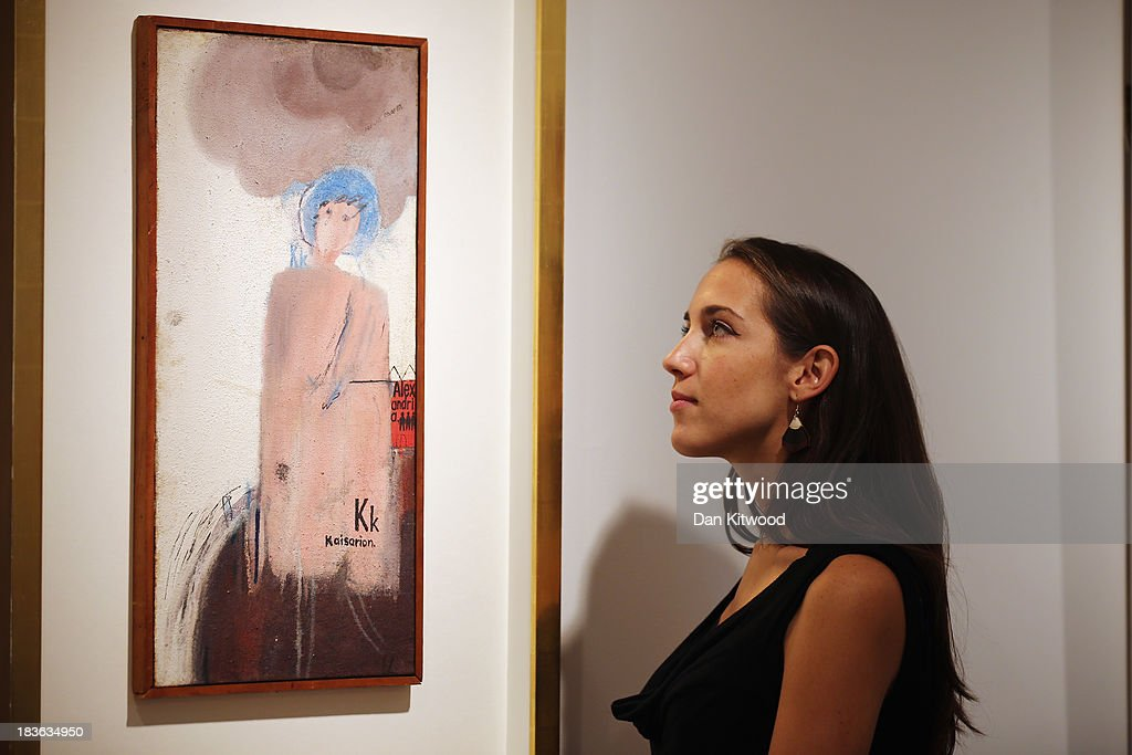 A Christie's employee poses beside an early piece of work by David Hockney during the 'When Britain went Pop!' exhibition at Christie's auction house on October 8, 2013 in London, England. The exhibition claims to be 'the first ever Comprehensive exhibition of British Pop Art to be held in London' and includes work by artists including David Hockney, Peter Blake, Richard Hamilton and Allen Jones and opens to the public until November 23.
