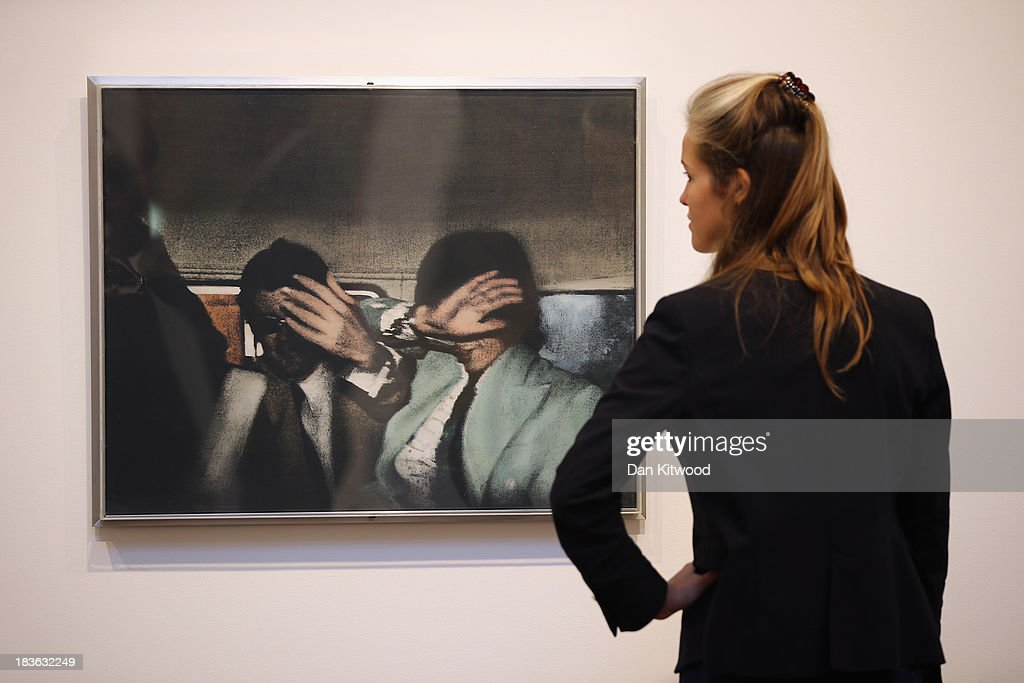 A Christie's employee poses besides a piece of work entitled 'Swingeing 60's' by Richard Hamilton during the 'When Britain went Pop!' exhibition at Christie's auction house on October 8, 2013 in London, England. The exhibition claims to be 'the first ever Comprehensive exhibition of British Pop Art to be held in London' and includes work by artists including David Hockney, Peter Blake, Richard Hamilton and Allen Jones and opens to the public until November 23.