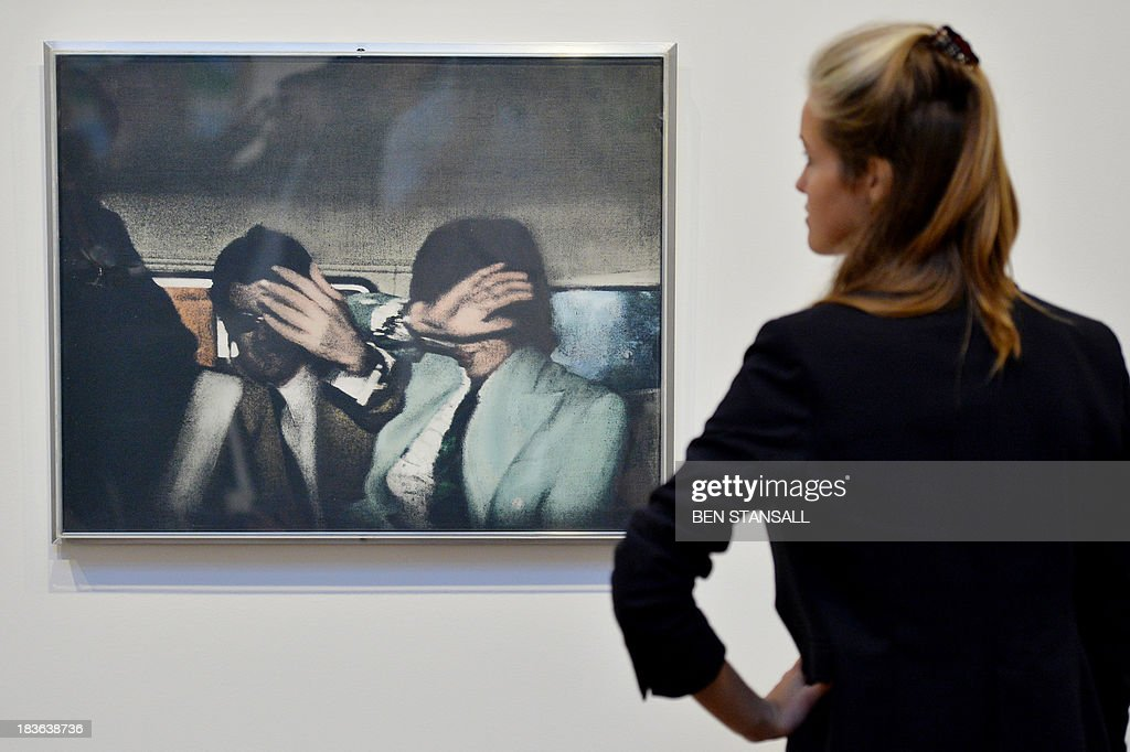A Christie's employee poses for pictures with a work of art entitled 'Swingeing 60's' by British artist Richard Hamilton during a photocall for an exhibition entitled 'When Britain Went Pop' at the auction house in London, on October 8, 2013. The exhibition aims to show how Pop Art began in Britain and how British artists like Richard Hamilton, Peter Blake, David Hockney, and Allen Jones shifted the boundaries between popular culture and fine art.