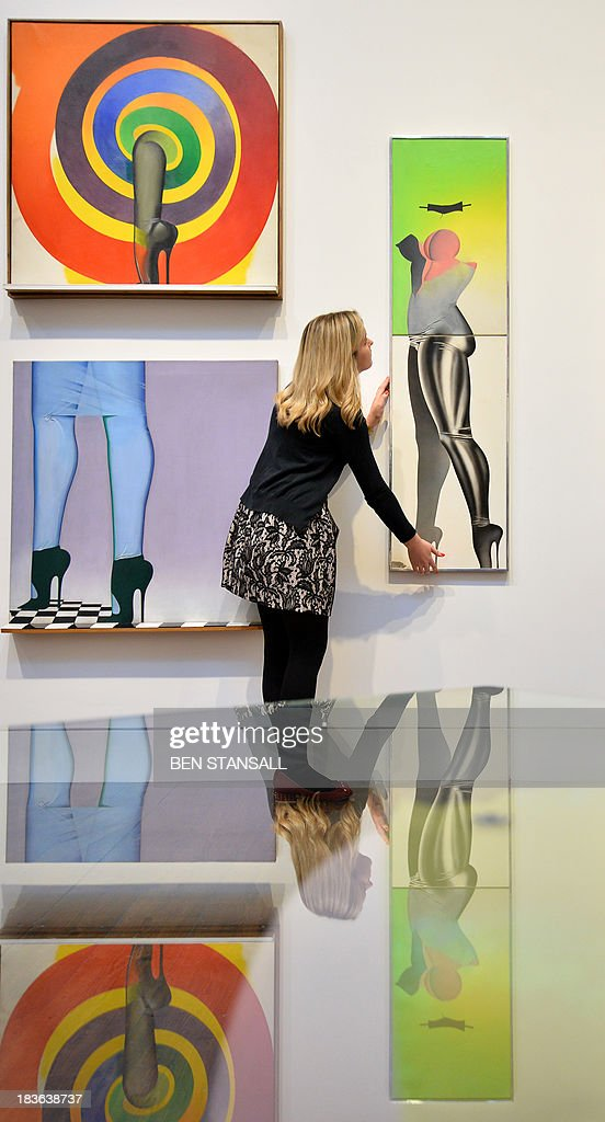 A Christie's employee poses for pictures with a work of art (R) entitled 'First Step' by British artist Allen Jones during a photocall for an exhibition entitled 'When Britain Went Pop' at the auction house in London, on October 8, 2013. The exhibition aims to show how Pop Art began in Britain and how British artists like Richard Hamilton, Peter Blake, David Hockney, and Allen Jones shifted the boundaries between popular culture and fine art. AFP PHOTO / BEN STANSALL
