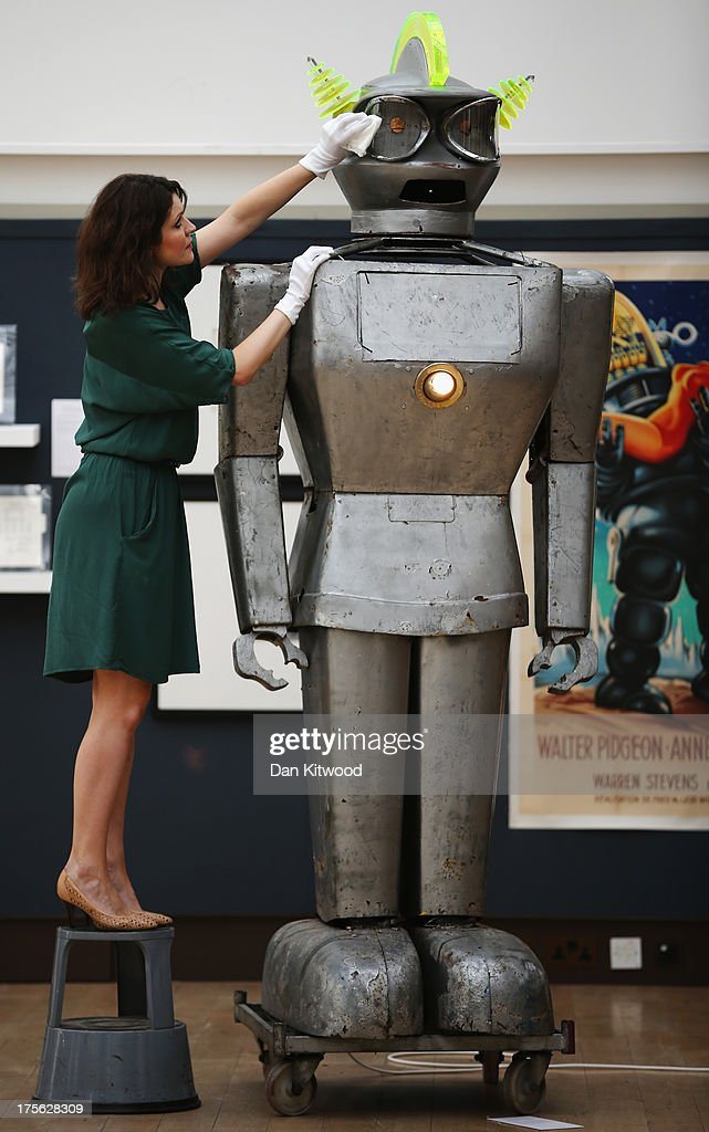 A Christie's employee poses next to 'Cygan', a giant robot at Christie's Auction House on August 5, 2013 in London, England. The robot makes up part of the 'Out of the Ordinary' sale at Christie's Auction House, and is expected to fetch between £8,000 -£12-000 GBP when it goes on sale on September 5, 2013.