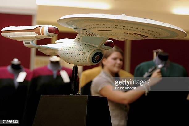 Christies employee poses with a Star Trek phaser behind a model of the Starship EnterpriseC on August 2 2006 in London Christie's New York are...