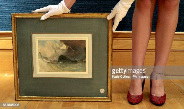 A Christie's employee stands beside the watercolour 'The Mew Stone off Plymouth Harbour' by Joseph Mallord William Turner It is expected to fetch...