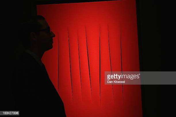 Christies employee stands in front of a piece of work entitled 'Concetto Spaziale' by Lucio Fontana during a press preview at Christies Auction House...