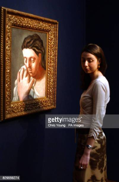 A Christie's employee stands near the painting