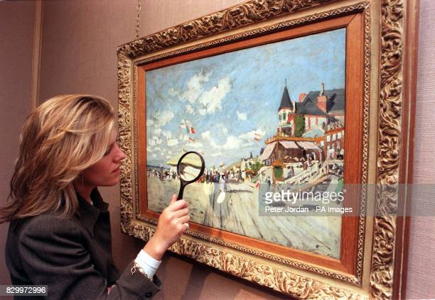 Christie's employee Victiria Coode looks at Sur les planches de Trouville by Claude Monet during a photocall in London this morning The painting...