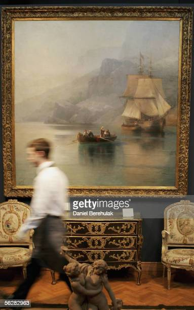 Christie's Employee walks past a painting A Fishing Boat With Russian Merhcant Brig At Anchor by celebrated Russian painter Ivan Konstantinivich...
