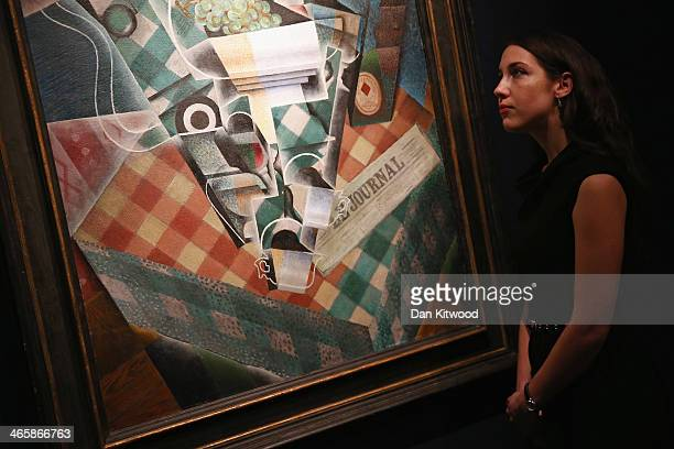 Christie's employees pose besides a piece of work entitled 'Nature morte a la nappe a carreaux' by Juan Gris at Christie's auction House on January...