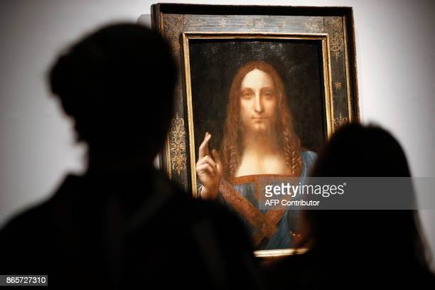 Christie's employees pose in front of a painting entitled Salvator Mundi by Italian polymath Leonardo da Vinci at a photocall at Christie's auction...