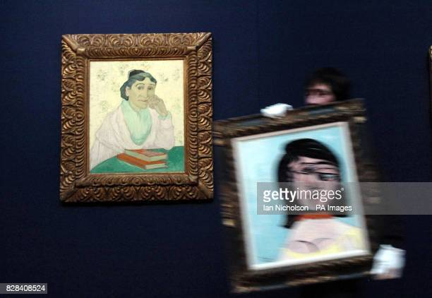 A Christie's porter carries a Picasso artwork Tete De Femme past the Van Gogh masterpiece L'Arlesienne Madame Ginoux at the auctioneer's London...