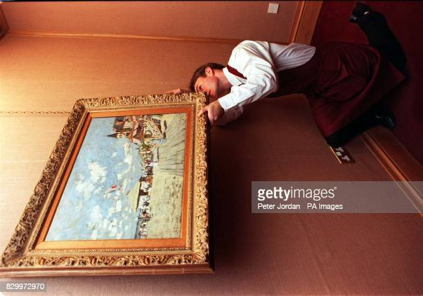 A Christie's porter hangs the Sur les planches de Trouville by Claude Monet during a photocall in London this morning The painting which has not been...